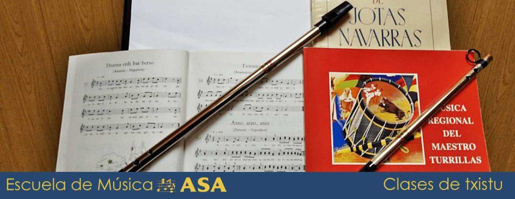 Libro de música, partituras y dos poxpolines sobre un atril